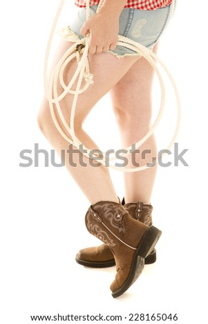 A woman's legs with boot and a rope. - stock photo