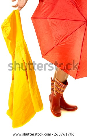 a woman 's legs with her umbrella and rain coat, ready for the weather. - stock photo
