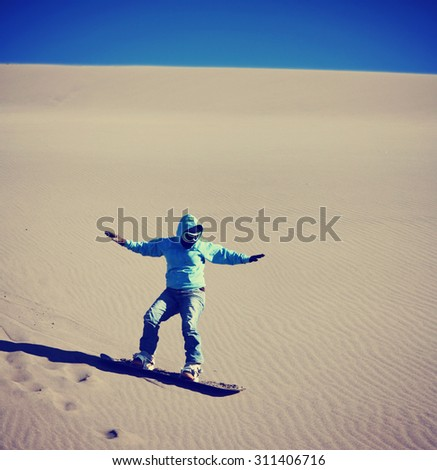 a woman sand boarding down a sandy dune hill with goggles and a sweatshirt hoodie on a snowboard toned with a retro vintage instagram filter effect app or action - stock photo