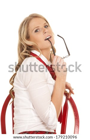 A woman school girl sitting in a chair chewing on her glasses. - stock photo