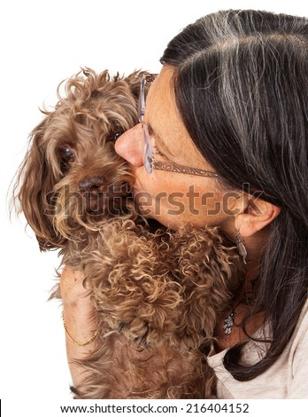 A woman shelter volunteer kissing the cheek of an elderly mixed breed rescue dog.