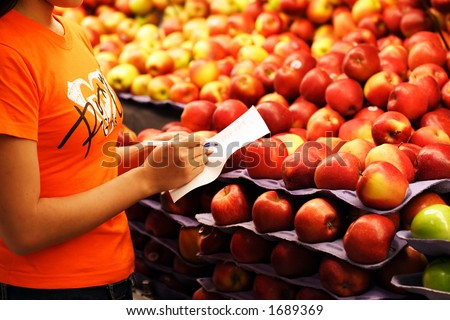 A woman shopping for apples at a grocery store