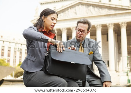 A woman showing a coworker or friend something in her valise. - stock photo