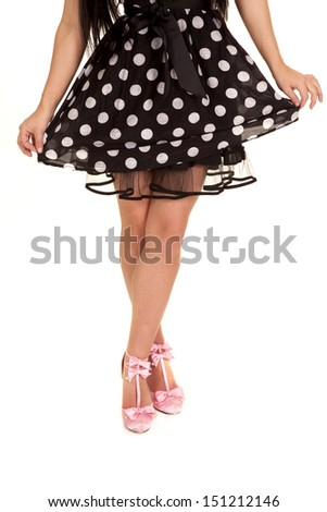 A woman showing off her polka dot dress and pink shoes. - stock photo