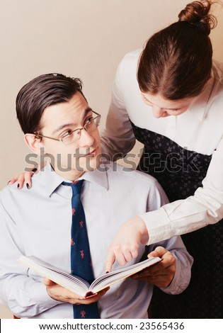 A woman showing something ot a man in a book