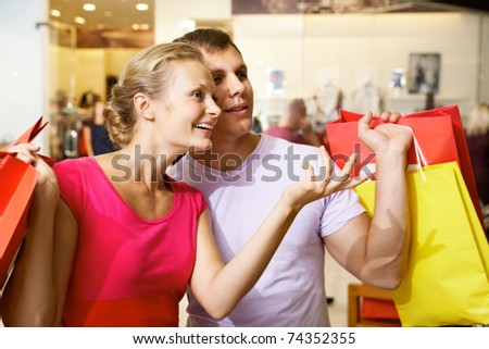 A woman showing something to her husband in supermarket