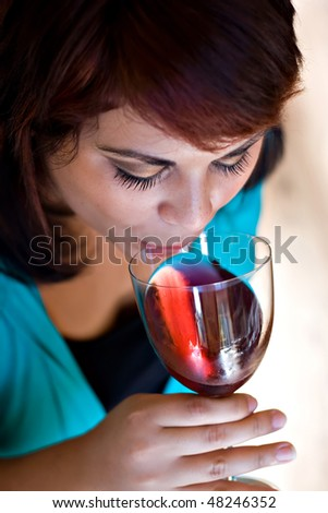 A woman sipping on her glass of red wine.  Shallow depth of field with focus on the eyelashes.