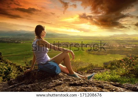 A woman sits on the edge of the cliff and looking at the sun valley and mountains - stock photo