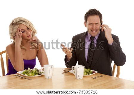 a woman sitting and being frustrated with her man because he is on the phone while they are having a nice dinner.  He is ignoring her. - stock photo