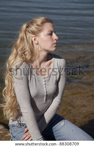 A woman sitting and thinking by the water. - stock photo