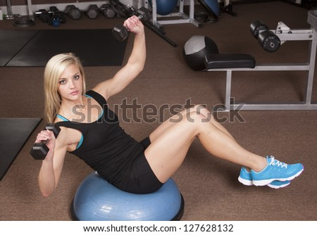 A woman sitting and working out with her weights.