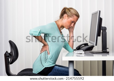 a woman sitting at a desk and has pain in the back. symbol photo for proper posture at work in the office. - stock photo