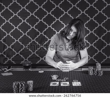 A woman sitting at a poker table playing cards in black and white - stock photo