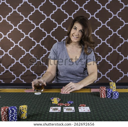 A woman sitting at a poker table playing cards with a brown background - stock photo