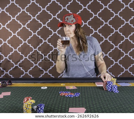 A woman sitting at a poker table wearing a red hat playing cards with a brown background - stock photo