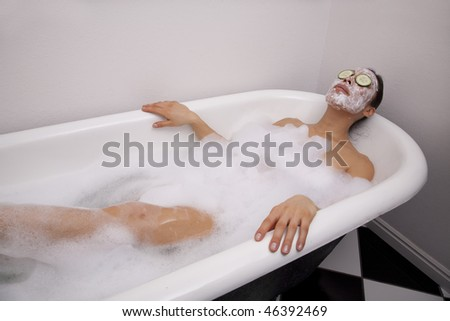 A woman sitting in a bath full of bubbles relaxing while wearing a facial mask.