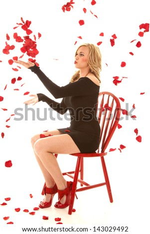 A woman sitting in a chair in her black dress throwing up rose petals. - stock photo