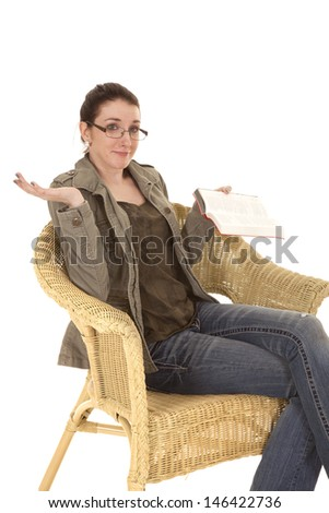 a woman sitting in a chair shrugging her shoulders while reading a book - stock photo