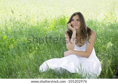 A woman sitting in a meadow smiles to herself whilst daydreaming