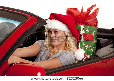 A woman sitting in her car driving down the road in her Santa hat with a present in her back seat. - stock photo
