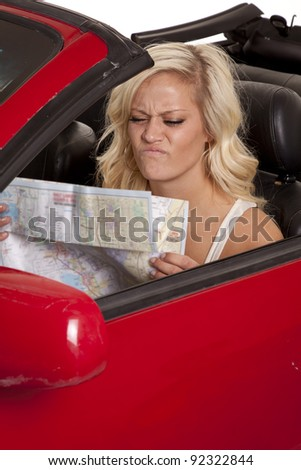 A woman sitting in her car with a frustrated expression on her face looking down at a road map. - stock photo