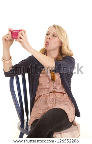 a woman sitting in her chair taking a picture of herself with her cell phone, while she sticks out her tongue. - stock photo