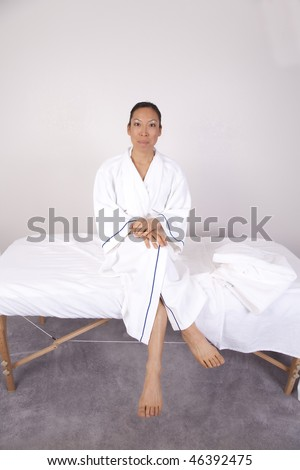 A woman sitting in her white robe on a massage table ready to get a massage.