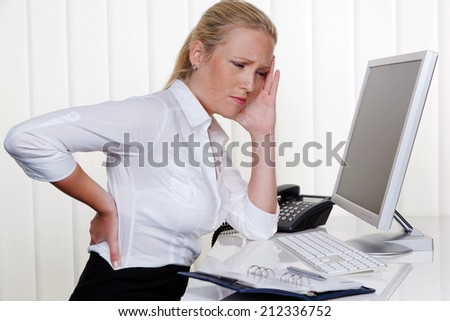 a woman sitting in office front of her computer and has back pain.