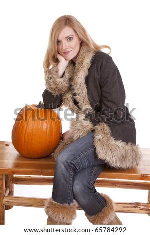 A woman sitting on a bench in her warm fuzzy coat while she leans on a pumpkin. - stock photo