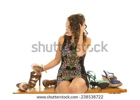 a woman sitting on a bench looking at all of her shoes.