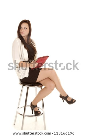 a woman sitting on a stool looking away. - stock photo