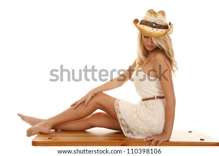 A woman sitting on a wooden bench with her knees up looking down. - stock photo