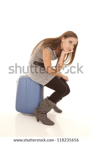 a woman sitting on her luggage waiting to go. - stock photo