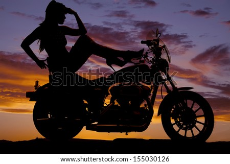 A woman sitting on her motorcycle with her shoes on the tank. - stock photo