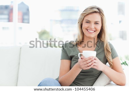 A woman sitting on the couch with a cup in her hands and smiling as she looks in front of her.