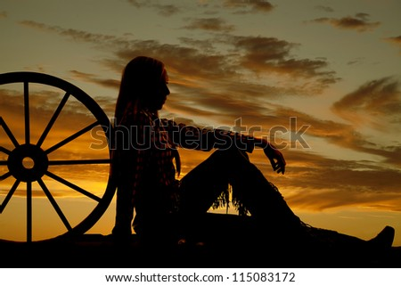 A woman sitting on the ground next to a wagon wheel with her chaps on.