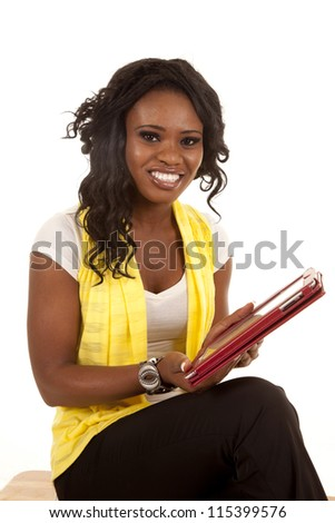 a woman sitting with a smile on her lips holding on to her electronic tablet. - stock photo