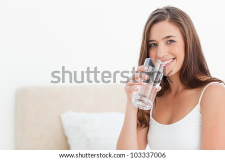 A woman smiling as she holds a glass of water to her mouth.