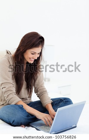 A woman smiling as she looks at her laptop with her legs crossed on the bed - stock photo