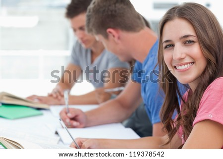 A woman smiling at the camera while her friends sit beside her looking at the homework they have - stock photo