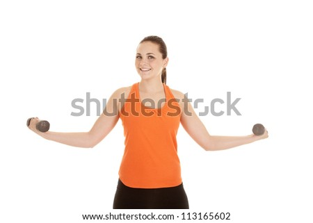 A woman smiling lifting weights in her hands gaining strength - stock photo