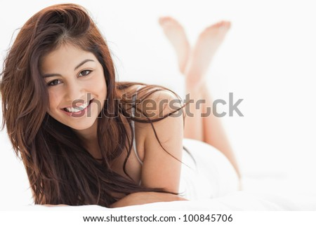 A woman smiling with her crossed arms on the bed, her legs raised and crossed. - stock photo