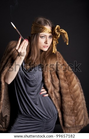 a woman smokes a cigarette with a mouthpiece on a black background in a mink coat - stock photo