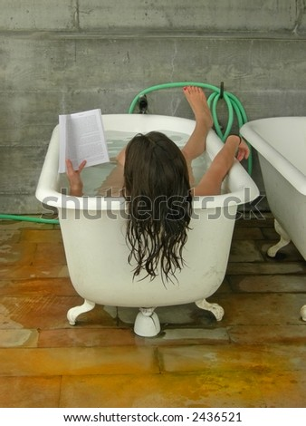 A woman soaks in a tub while reading. - stock photo