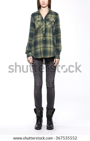 A woman stand up wearing black denim(pants, trousers, jean) and black leather boots and green(khaki) check pattern shirts for fall, outdoor isolated white at the studio.  - stock photo