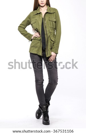 A woman stand up wearing black denim(pants, trousers, jean) and black leather boots and khaki military jacket(jumper) for winter, fall isolated white at the studio.  - stock photo