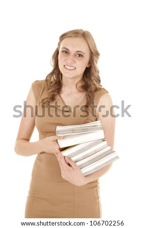 A woman standing and holding on to a stack of books with a smile on her face. - stock photo