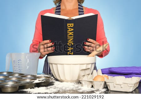 A woman standing at a kitchen worktop reading a BAKING A-Z book  - stock photo