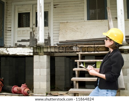 A woman standing in front of an old dilapidated house wearing a hard hat and holding a clipboard. - stock photo