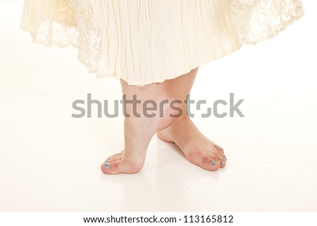 a woman standing in her bare feet in her lace dress. - stock photo